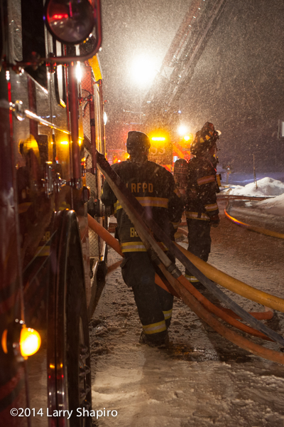 firemen battle house fire in snow storm at night