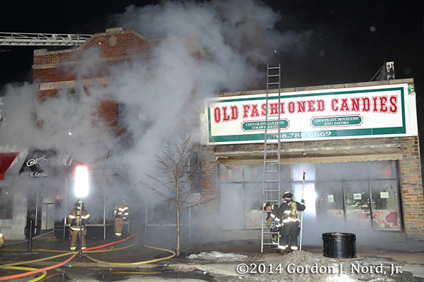 firemen battle smokey commercial fire at night