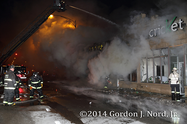 firemen battle smokey fire at night in retail store