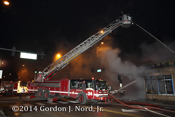 Chicago FD E-ONE Tower Ladder 34 working at a night fire scene