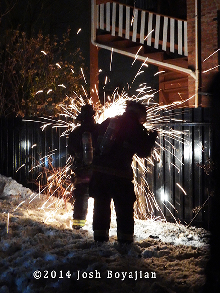 firemen cut metal fence at night
