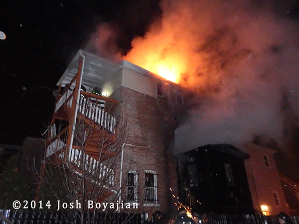 fire burns through the roof of a two-story house