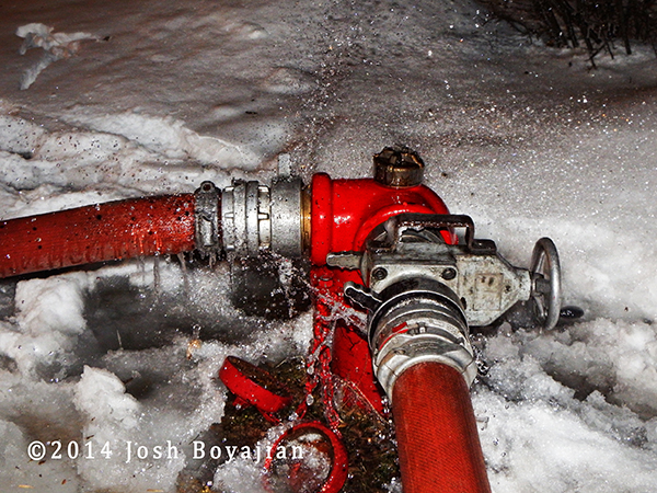 fire hydrant in the snow with hose attached
