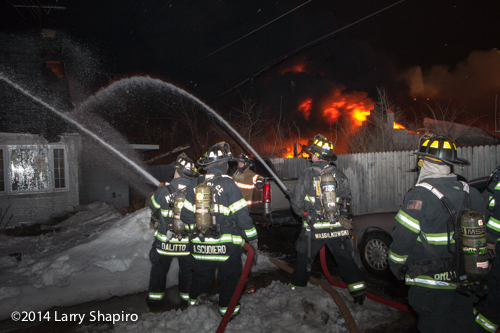 firemen at night with hose line