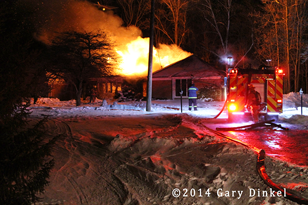 night photo of house fully engulfed in flames