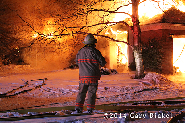 chief fire officer at fully engulfed house fire at night