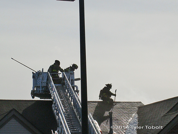firemen working on roof of building