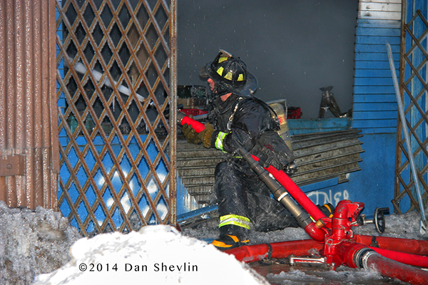 iceman with fire hose at fire scene