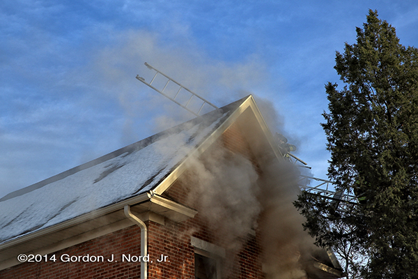 smoke escapes from a house on fire