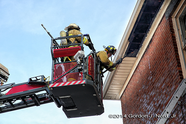 firemen work from tower ladder basket