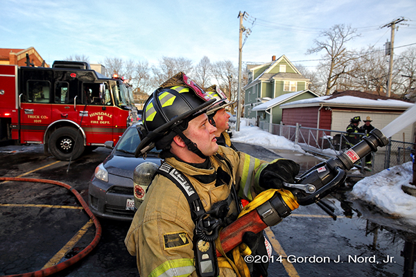 fireman with hose line at fire scene