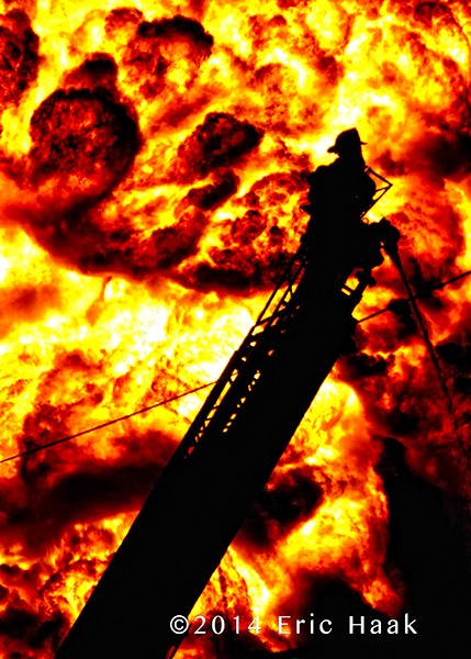 silhouette of fireman on ladder with massive flames