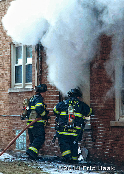 firemen with hose line at apartment building fire