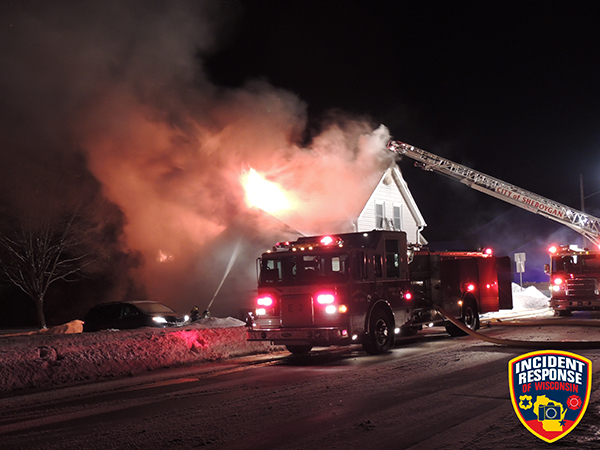 flames through the roof of house at night