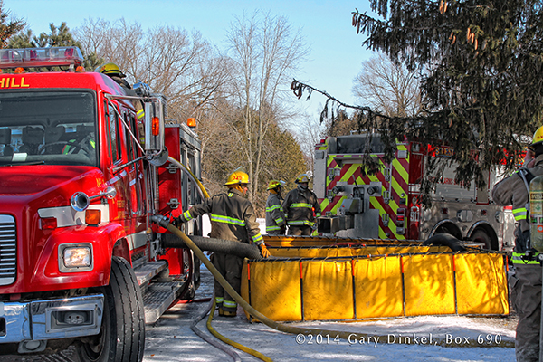 fire engine drafts from portable tank at winter fire