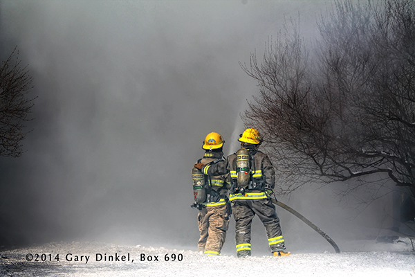 firemen with hose line at winter fire scene with wall of smoke