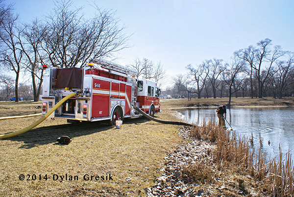 fire engine drafting water from a pond