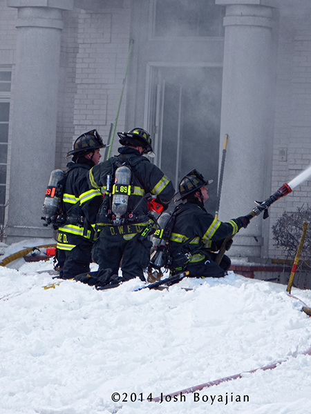 firefighters with hose at winter fire scene