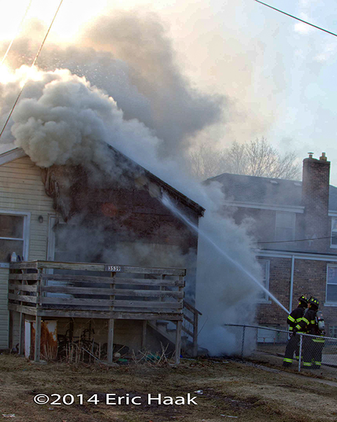firemen with hose attack house fire with heavy smoke