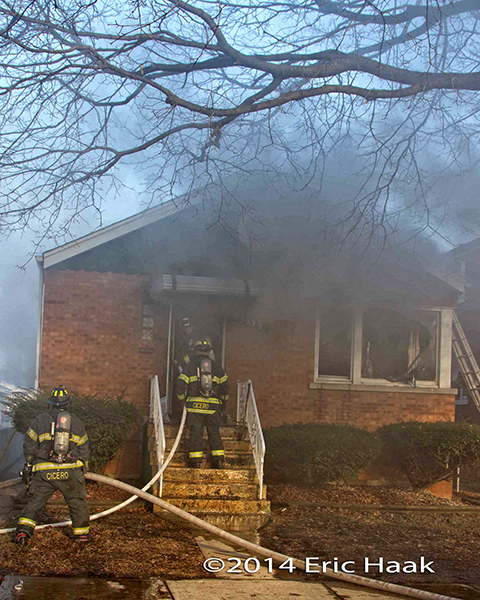 firemen with hose enter house on fire