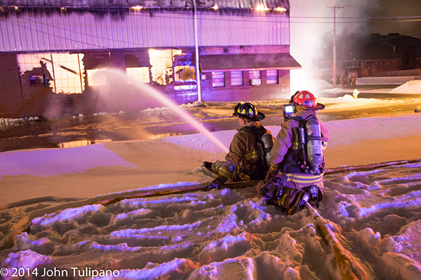 firemen with hose at huge night time fire