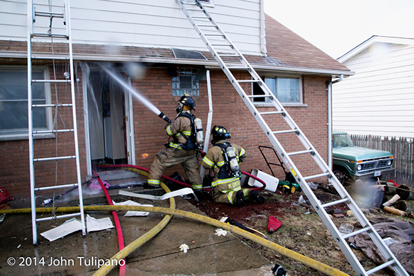 firemen with hose line at house fire