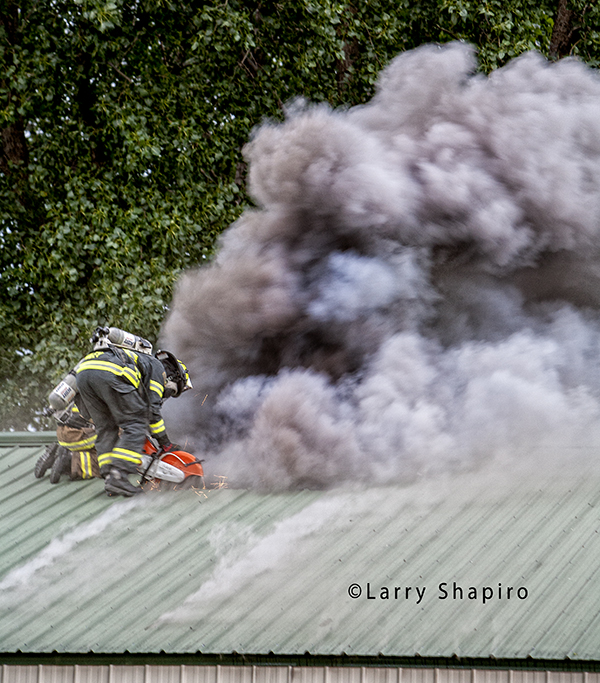 firemen ventilating corrugated roof