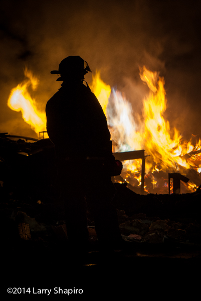 firefighter silhouetted by fire