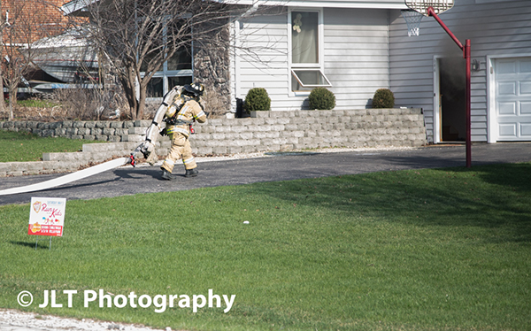 fireman pulling hose at fire scene