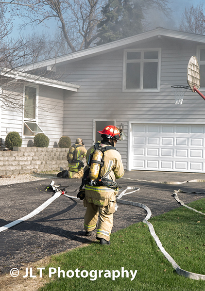 fireman entering house to extinguish fire