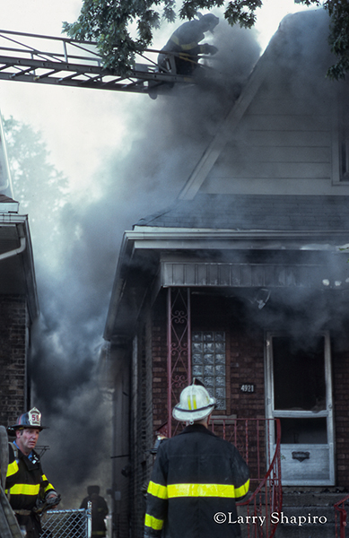 firemen battle a house fire with smoke and flames