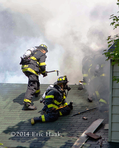 firemen on roof of house with heavy smoke