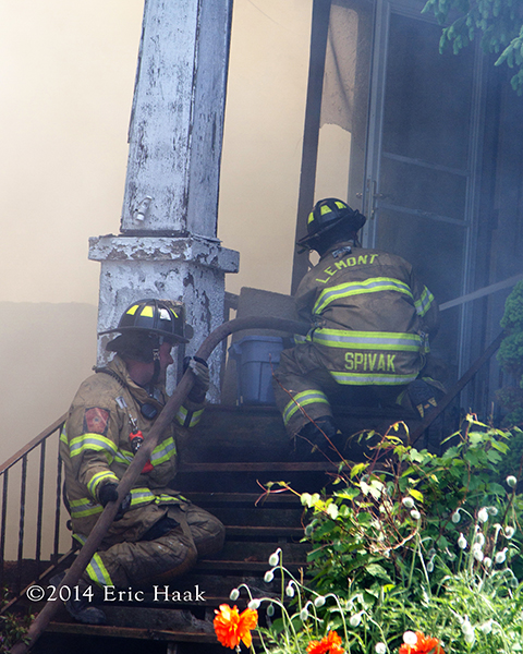 firemen with hose on steps of house