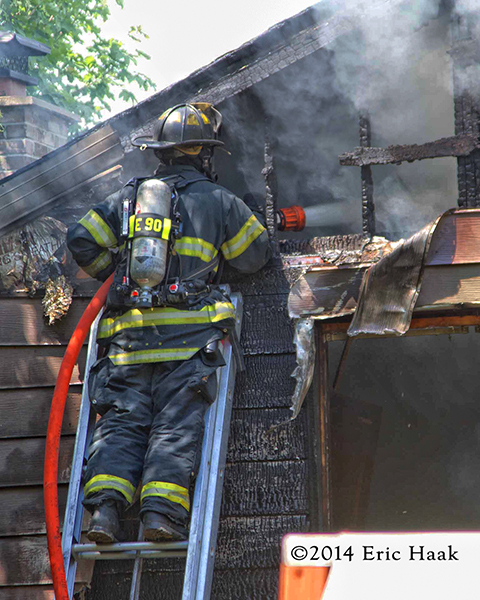 fireman in gear on ladder with hose