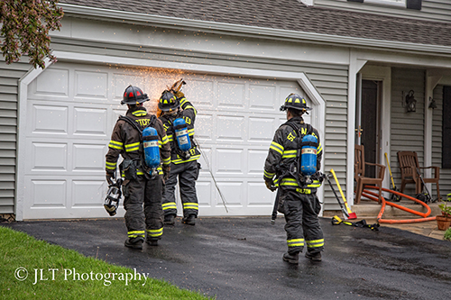 firemen cut garage door at fire scene