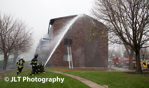 firemen throw water at building fire