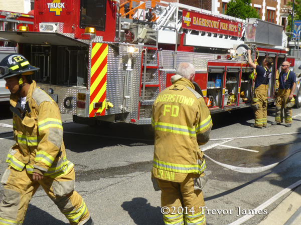 fireman picking up hose after fire