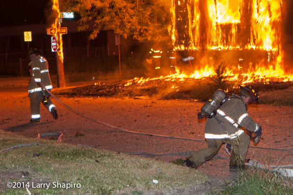 Detroit firefighter stretching a line