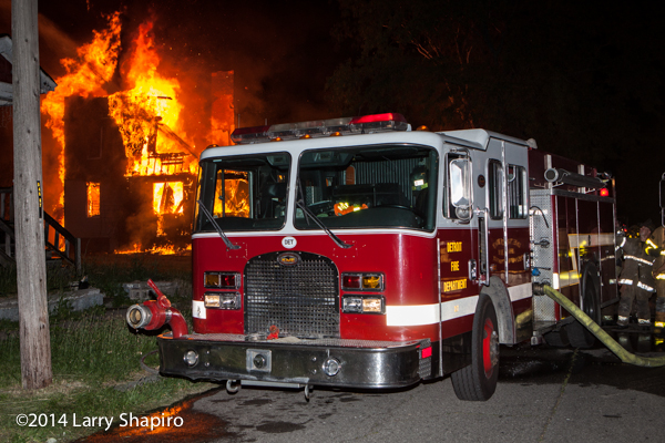 Detroit fire engine with burning structure at night