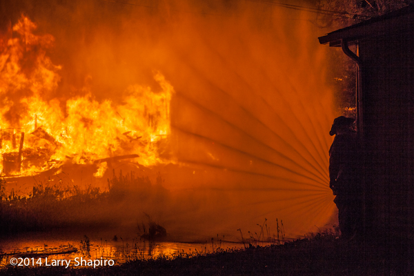 fireman silhouette with hose line and fire
