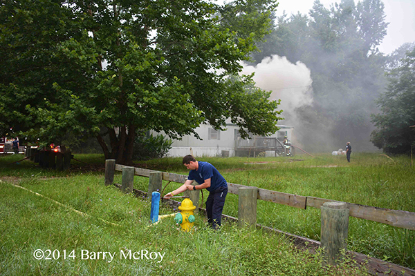firefighter hooks hose to hydrant