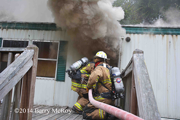 firemen take a hose into a burning mobile home