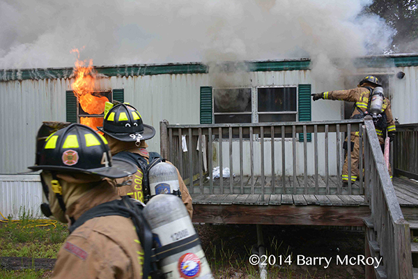 firemen enter a burning mobile home
