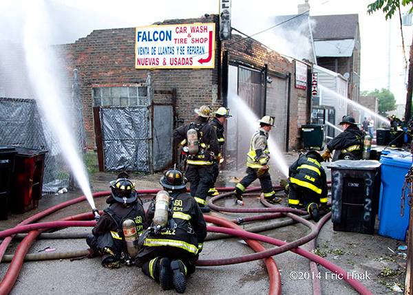 Chicago firemen operate hoselines at fire scene