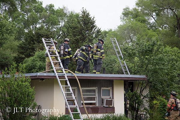 firemen work on the roof of a house after a fire
