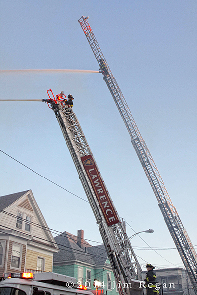 aerial ladder pipes working at fire scene