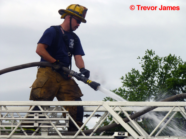 fireman cleans ladder truck after fire
