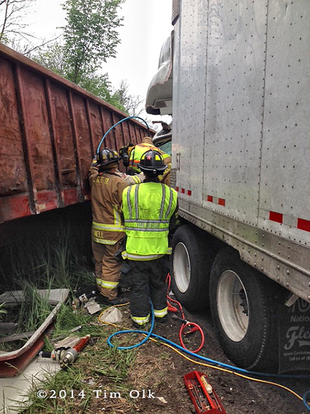 firemen work to free truck driver from crushed cab