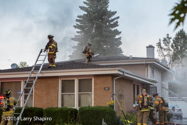 firemen climb to the roof of a house to ventilate the smoke during a fire