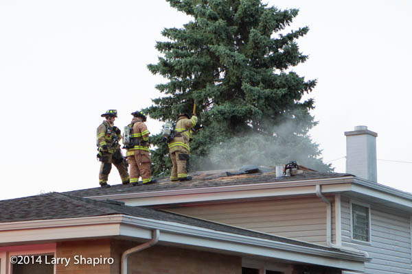 firemen ventilate roof of a house